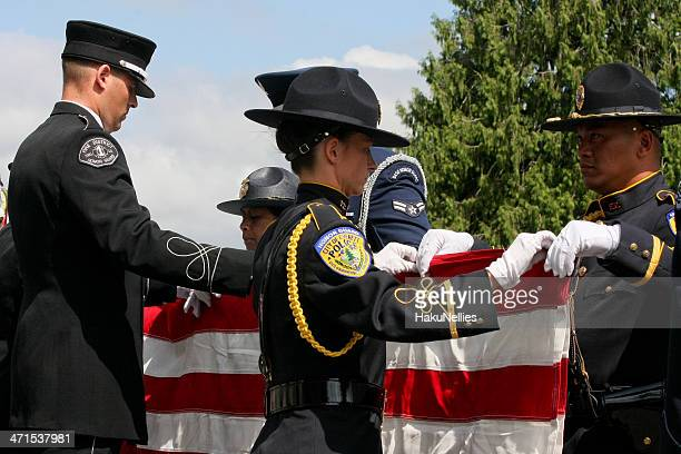 officers folding the american flag at a memorial service - air force memorial stock pictures, royalty-free photos & images