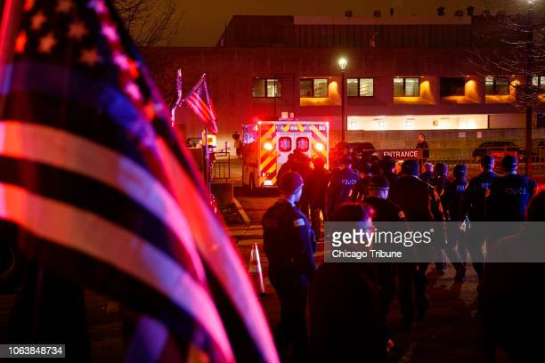 Officers follow an ambulance as it arrives at the medical examiners office carrying the body of a police officer who was killed during a shooting at...