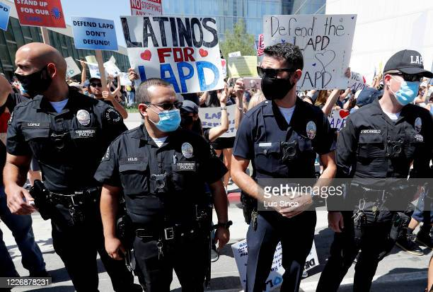 Officers form a line to separate pro- and anti-police demonstrators outside LAPD headquarters in downtown Los Angeles on Saturday, July 11, 2020....
