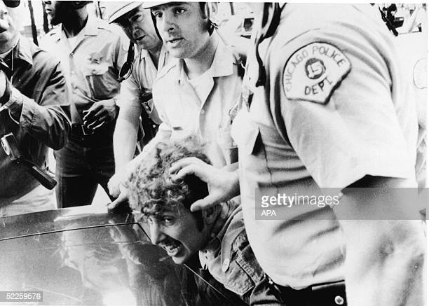 Officers from the Chicago Police Department push a protestor's head against the hood of a car as they restrain him after he climbed onto a wooden...