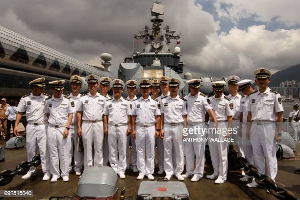 Officers from the Command of the People's Liberation Army Hong Kong Garrison pose on the deck of the Russian guided missile cruiser Varyag during a...