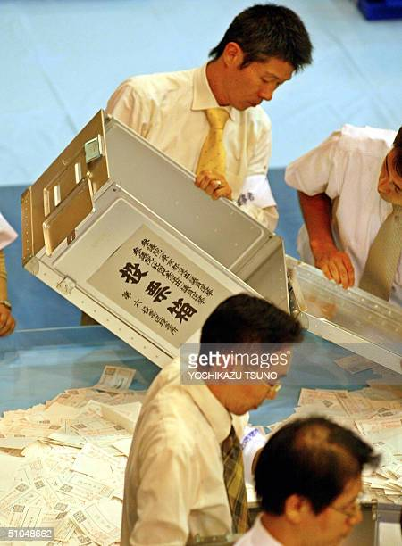 Officers from the election administration committee open ballot boxes to count at an election office in Tokyo following Japan's Upper House election...