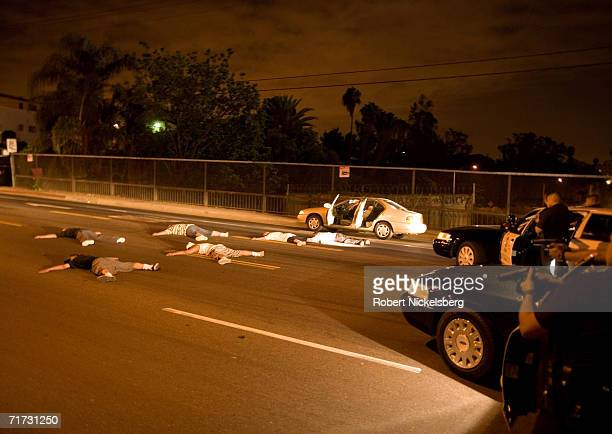 Officers from the Los Angeles Police Department gang unit aim their pistols at a stolen car stopped on a freeway bridge filled with 6 possibly armed...