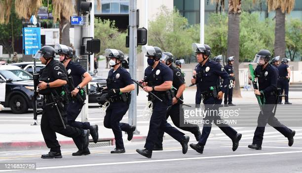 Officers from the Los Angeles Police Department run to formation during a march over the death of George Floyd, an unarmed black man, who died after...