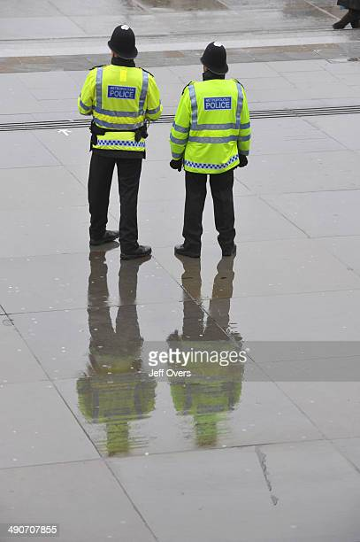 Officers from the Metropolitan Police stand in a rainy Trafalgar Square in London Men officer fluorescent yellow jacket jackets Met bobbies helmet...