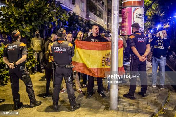 Officers from the Mossos d'Esquadra police force block the route of protesters carrying a Spanish national flag during a demonstration organised by...