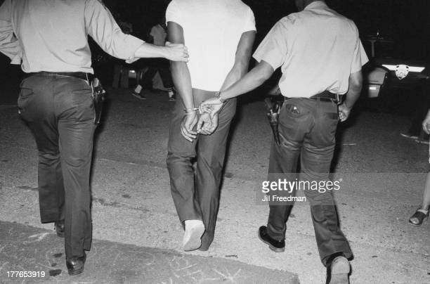 Officers from the NYPD 9th Precinct handcuff and arrest a man New York City 1980