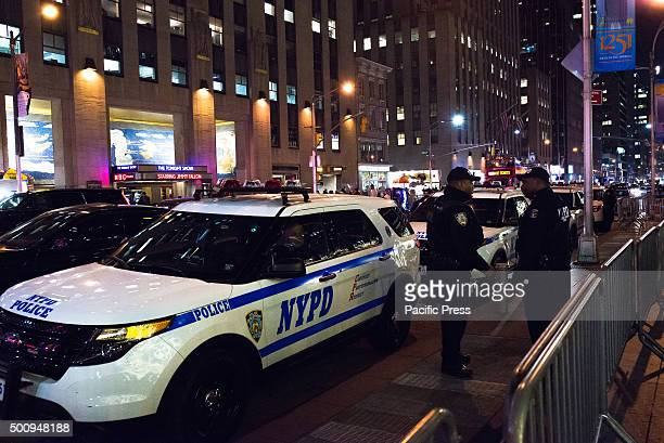 Officers from the NYPD's Strategic Response Group stand alert by their service vehicles on Seventh Avenue Amid growing concern for the possibility of...