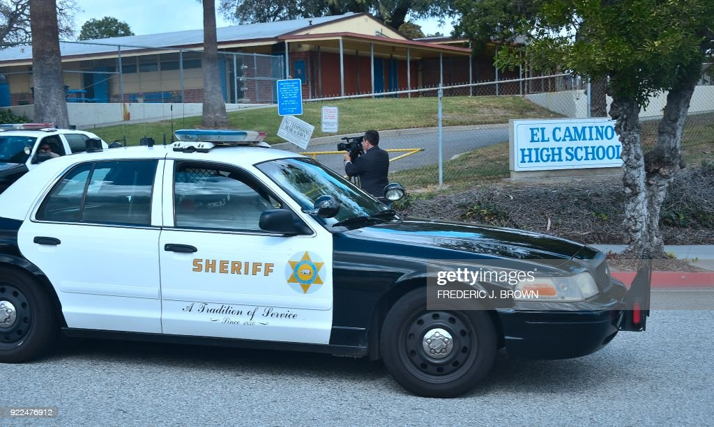 Officers from the Sheriff's Department drive through and past the campus of El Camino High School in Whittier, California on February 21, 2018 where a threat by a student overheard by a school safety officer may have stopped a shooting. Authorities were alerted, leading to the finding of a cache of weapons in the teenager's home. Marino Chavez, a security officer at El Camino High School in Whittier, southeast of Los Angeles, helped thwart a potential shooting February 16, 2018, two days after the deadly Valentines Day shooting in Florida that left 17 people dead, authorities said February 21. Chavez said during a news conference he overheard a 17-year-old student say he was going to launch an attack within three weeks. Chavez stopped and questioned the student, who claimed it was a joke, he said. / AFP PHOTO / Frederic J. BROWN