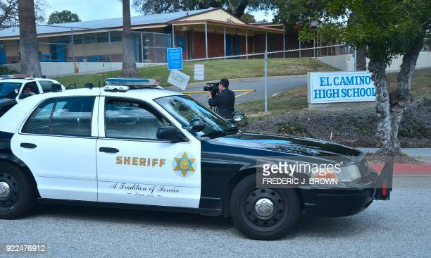Officers from the Sheriff's Department drive through and past the campus of El Camino High School in Whittier, California on February 21, 2018 where...
