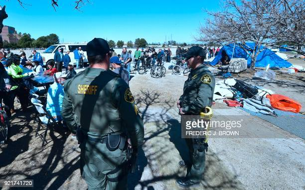 Officers from the Sheriff's Department stand and watch as homeless transients wait in line to meet with county officials beside the Santa Ana River...