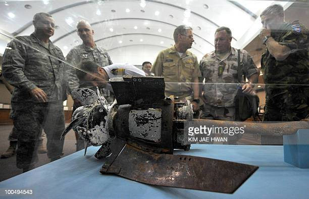 Officers from the United Nations Command inspect a broken section of what Seoul claims to be a North Korean torpedo which was salvaged near the...
