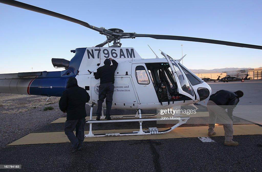 Officers from the U.S. Office of Air and Marine prepare a helicopter for an aerial patrol on February 26, 2013 in Tucson, Arizona. The U.S. Customs and Border Protection agency flies over the U.S.-Mexico border searching for drug smuglers entering the United States from Mexico.