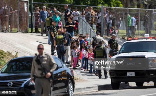 SWAT officers help evacuate children to awaiting school buses after a shooting inside North Park Elementary School on April 10 2017 in San Bernardino...