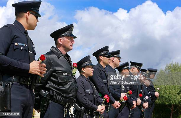 Officers hold roses for their comrade, LAPD officer Nicholas C. Lee, who was killed March 7 when his patrol car collided with a commercial vehicle in...