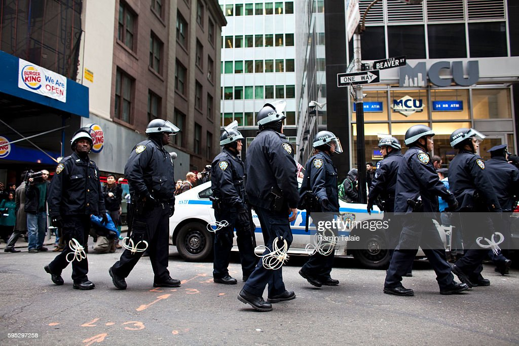 NYPD officers in riot gear follow protestors with Occupy