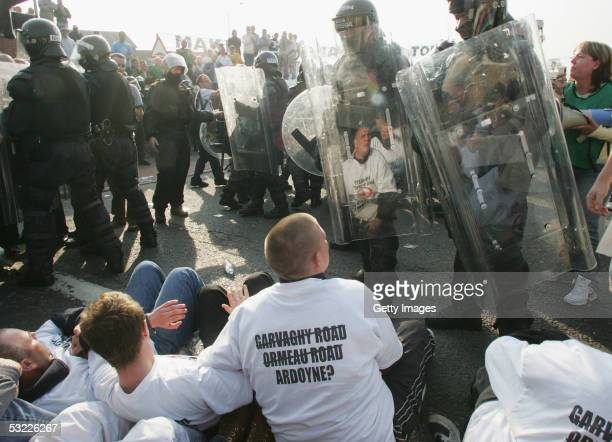 Officers in riot gear move in to tackle sit - down protesters on Crumlin Road on July 12, 2005 in Belfast, Northern Ireland. Catholic residents of...