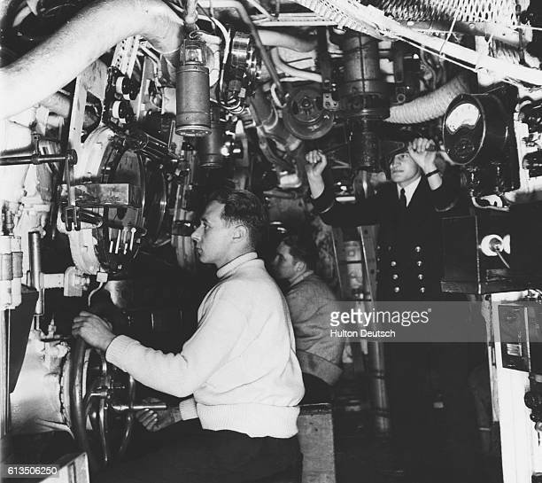 Officers in the control room of a British submarine during WWII The commander is operating the periscope