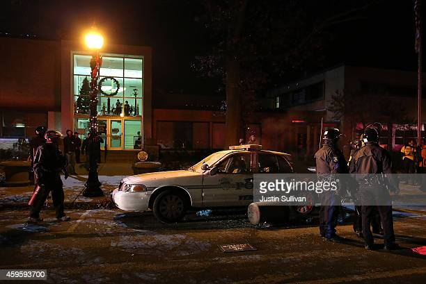 Officers investigate a Ferguson police car in front of City Hall after protestors damaged it on November 25 2014 in Ferguson Missouri Over 2000...