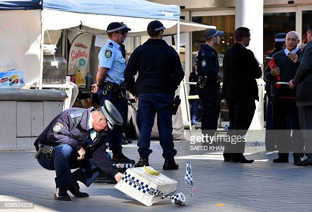 Officers investigate the scene of a police shooting at the shopping arcade in the Hornsby area of Sydney on June 9 2016 Three elderly bystanders were...