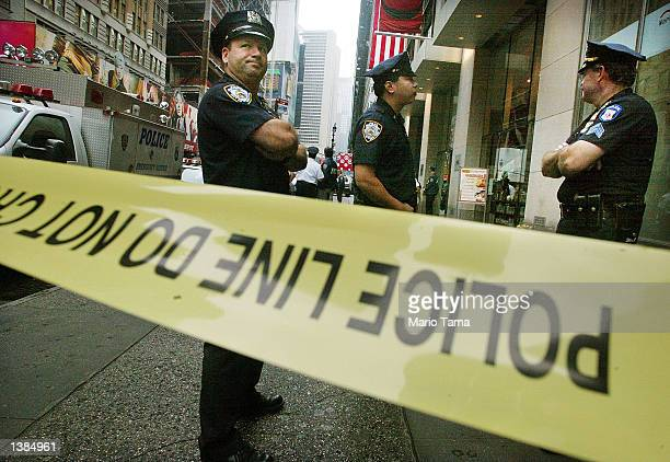 NYPD officers keep watch outside an office building near Times Square where three people were killed in a shooting September 16 2002 in New York City...