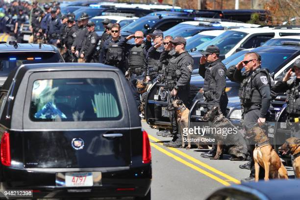 K9 officers line Higgins Crowell Road in Yarmouth MA and salute the hearse as the funeral procession for slain Yarmouth K9 officer Sean Gannon makes...