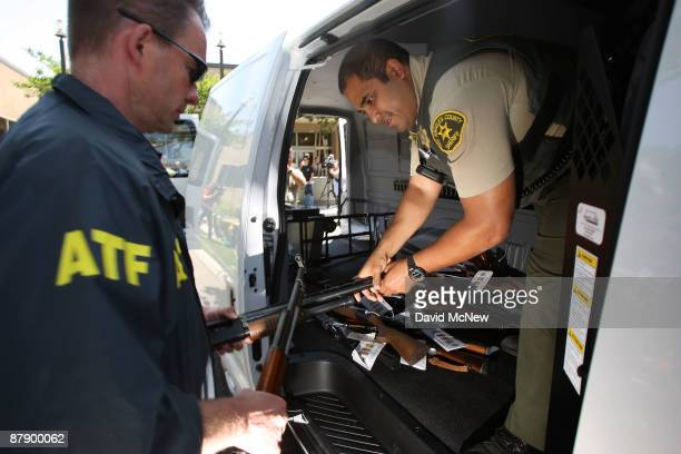 Officers load some of about 125 weapons confiscated during what the federal authorities say is the largest gang takedown in United States history...