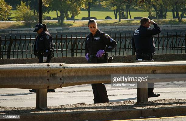 NYPD officers look for evidence at the FDR Drive as investigations continue after a NYPD officer was killed in a confrontation with an armed suspect...