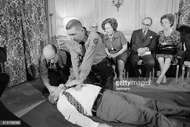 Officers of NYC Police Department's emergency service section give a demonstration on external cardiac massage during news conference here announcing...