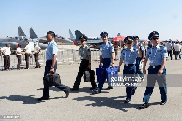 Officers of the China Peoples' Liberation Army Airforce walk between the stalls at the exhibition area on the second day of the 11th edition of 'Aero...