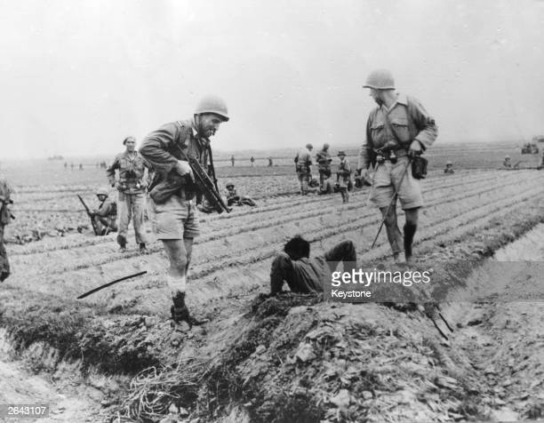 Officers of the French 1st RES unit pull a rebel out of a foxhole south east of Tonkin during the IndoChina War