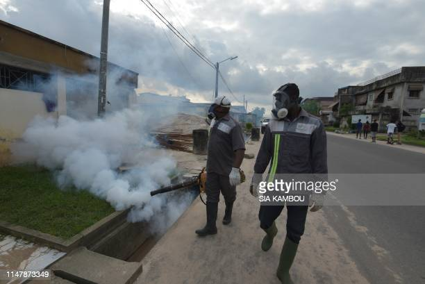 Officers of the National institute for public hygiene are at work to fumigate an area to prevent mosquitos from breeding on June 3 2019 in Abidjan as...