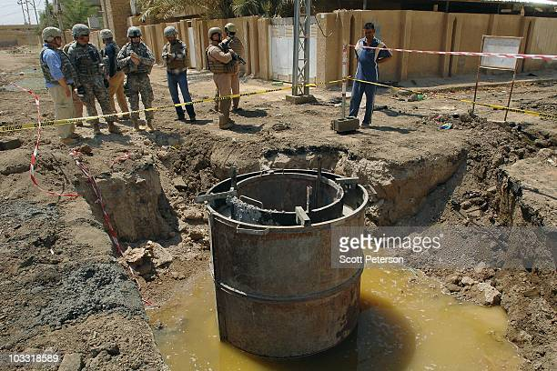 Officers of the US Army Corps of Engineers inspect USfunded manhole excavations in Fallujah Iraq on July 23 2010 The USACE has spent $190 million in...