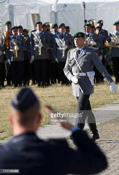Officers participate in a swearingin ceremony for new recruits of the Bundeswehr the armed forces of the Federal Republic of Germany in front of the...