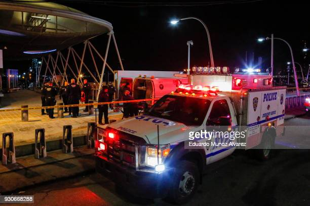 NYPD officers remove the bodies from the scene of a helicopter crash in the East River on March 11 2018 in New York City According to reports two...