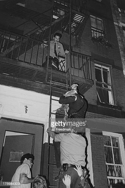 NYPD officers rescue a dog from a fire escape in Midtown Manhattan New York 1979