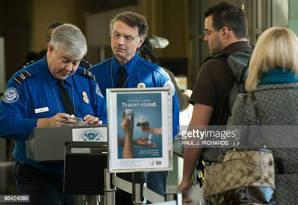 TSA Officers review air traveler's boarding passes and identification at a security checkpoint inside Ronald Reagan Washington National Airport...