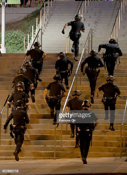 Officers run up the steps as they react to a protestors throwing rocks at them outside Grand Park on Broadway in Los Angeles, CA November 11, 2016....