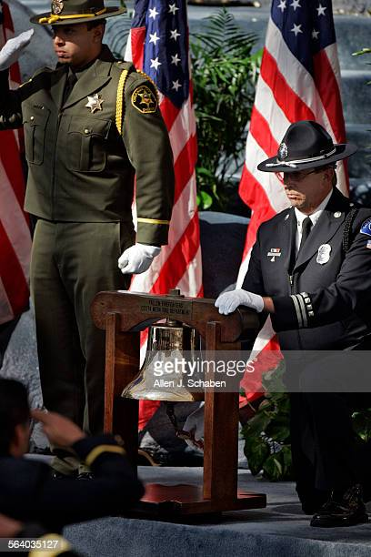 Officers salute during the tradition of the ringing of the bell, which is three sets of three rings to signal the end of an emergency and return to...