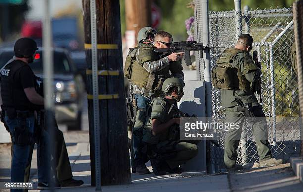 SWAT officers search near Victoria Elementary School on Richardson Street for the suspects involved in the mass shooting of 14 people at the Inland...
