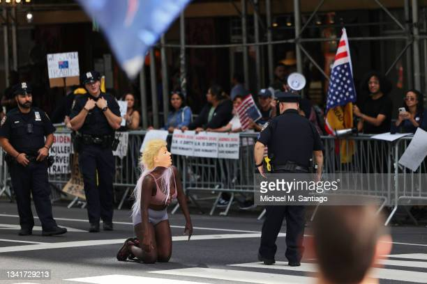 Officers speaks to a woman crawling on the ground wearing a mask of former President Donald Trump near the United Nations General Assembly on...