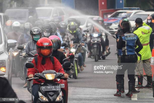 Officers spray disinfectant to motorists at border checkpoint Surabaya and its satellite cities during the large-scale social restrictions imposed by...