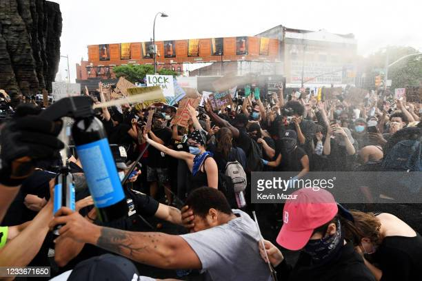 Officers spray mace into the crowd of protesters gathered at Barclays Center to protest the recent killing of George Floyd on May 29, 2020 in...