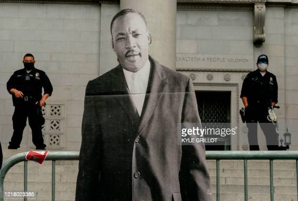 TOPSHOT LAPD officers stand behind a photo of Martin Luther King Jr during a demonstration over the death of George Floyd while in Minneapolis Police...