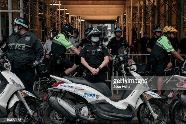 Officers stand by as a march against police brutality proceeds through Lower Manhattan on June 11, 2020 in New York City. Demonstrations against...