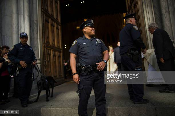 NYPD officers stand guard after the arrival of Cardinal Timothy Dolan to St Patricku2019s Cathedral for mass during the Annual Easter parade on April...