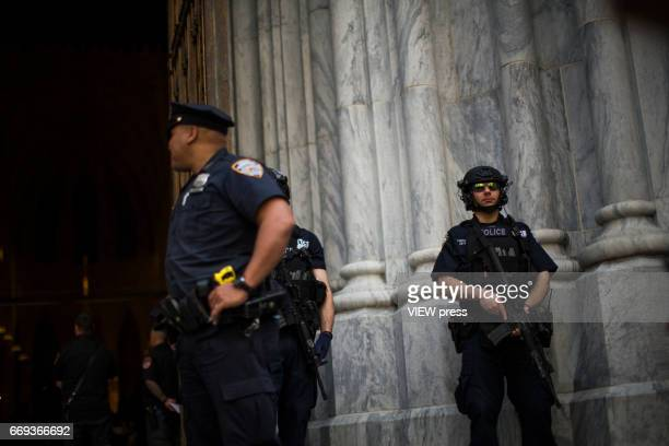 NYPD officers stand guard after the arrival of Cardinal Timothy Dolan to St Patrick'u2019s Cathedral for mass during the Annual Easter parade on...