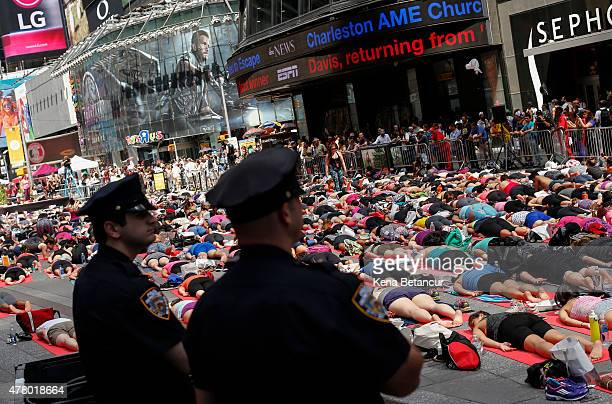 NYPD officers stand guard as people do yoga in Times Square as part of the International Day of Yoga celebration on the Summer Solstice June 21 2015...