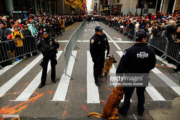 NYPD officers stand guard as people watch the 90th Macy's Annual Thanksgiving Day Parade on November 24 2016 in New York City Security was tight in...