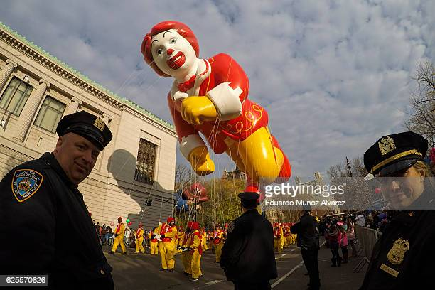 NYPD officers stand guard as revellers holding a Ronald MacDonald balloom walk down Central Park West during the 90th Macy's Annual Thanksgiving Day...